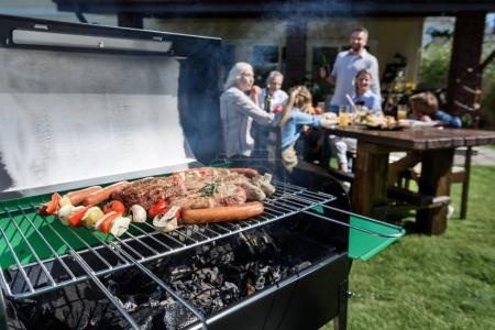 Photo for Family spend time together at barbecue. Selective focus of meat and vegetables cooking on grill - Royalty Free Image