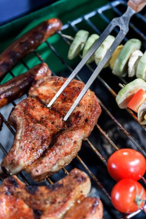 meat pricked by carving fork on grill