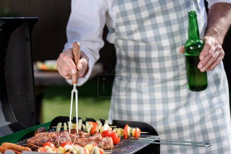 Photo for Cropped shot of man preparing meat and vegetables on grill and drinking beer from bottle - Royalty Free Image