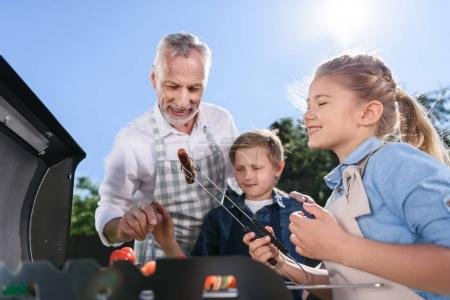 grandchildren with grandfather preparing sausages on grill
