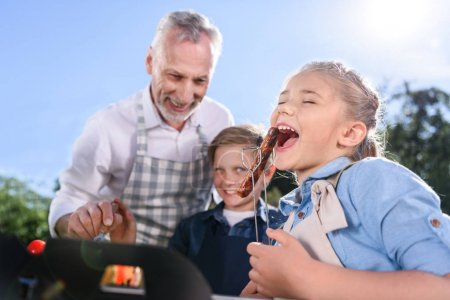 grandchildren with grandfather eating sausages on picnic