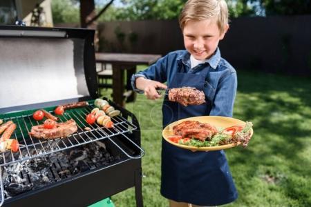 Kid boy preparing stakes on grill
