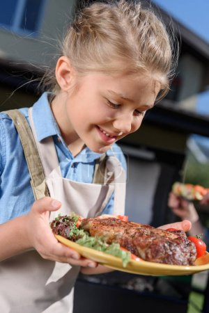 kid girl holding plate with steak