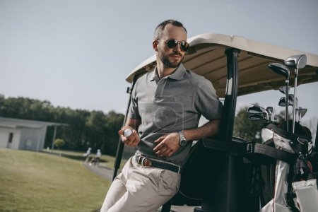 stylish golfer holding golf ball