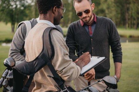 Photo pour Homme afro-américain écrit dans le presse-papiers tout en regardant deux joueurs de golf - image libre de droit