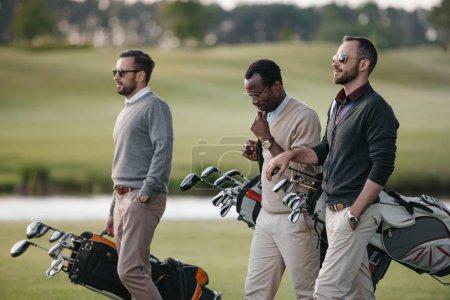 Photo pour Golfeurs multiethniques tenant des sacs avec des clubs de golf et marchant sur le terrain de golf - image libre de droit