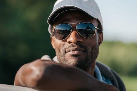 Photo pour Gros plan portrait d'un bel homme afro-américain en casquette et lunettes de soleil - image libre de droit