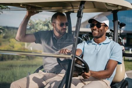 men riding golf cart