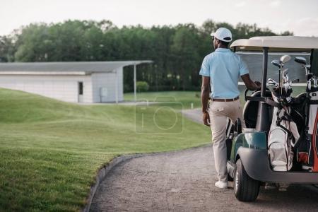 Photo pour Golfeur afro-américain regardant loin tout en se tenant près de voiturette de golf - image libre de droit
