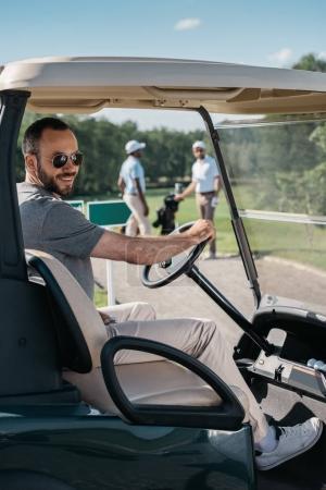 young man sitting at golf cart