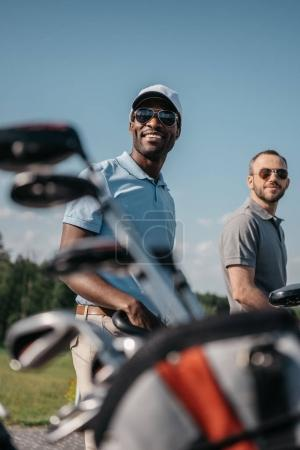 Smiling sportsmen going to golf course