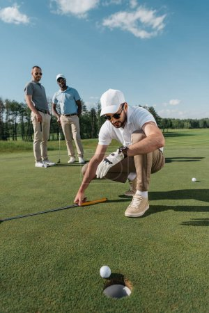 Golf player looking at ball near hole