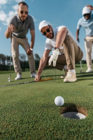 golf players looking at ball near hole