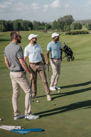 multiethnic golf players looking away