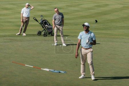 Photo pour Jeunes sportifs multiethniques debout avec des clubs de golf sur terrain vert - image libre de droit
