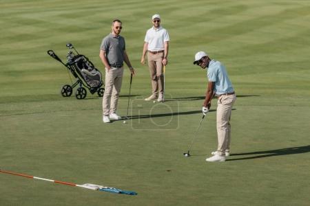 Photo pour Golfeur afro-américain prendre un coup avec club de golf tandis que ses amis debout derrière sur vert - image libre de droit
