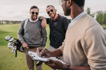 Photo pour Homme élégant dans les lunettes de soleil document de signature sur le terrain de golf - image libre de droit