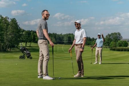 Photo pour Amis souriants parler tout en jouant au golf ensemble sur le vert pendant la journée - image libre de droit