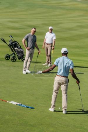 Foto de Jóvenes golfistas multiétnicos hablando durante el juego sobre césped verde durante el día - Imagen libre de derechos