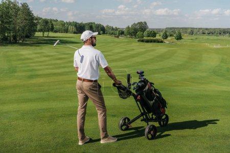 Photo pour Jeune joueur de golf regardant loin tout en se tenant avec le sac et le club sur le terrain vert - image libre de droit