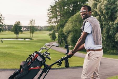 Photo pour Souriant afro-américain dans lunettes de soleil marchant avec sac plein de clubs de golf - image libre de droit