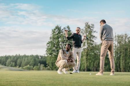 Photo for Stylish multicultural friends spending time together while playing golf on golf course - Royalty Free Image