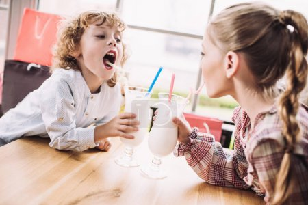 Children drinking milkshakes with straws