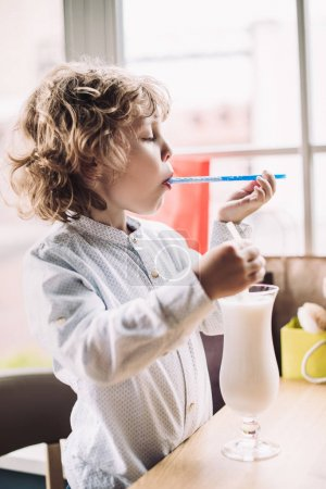 Boy licking straw and holding milkshake