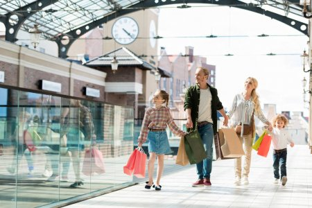 Photo pour Famille avec des sacs à provisions tenant la main tout en marchant dans le centre commercial - image libre de droit