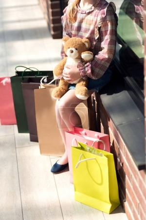 Girl with shopping bags holding teddy bear