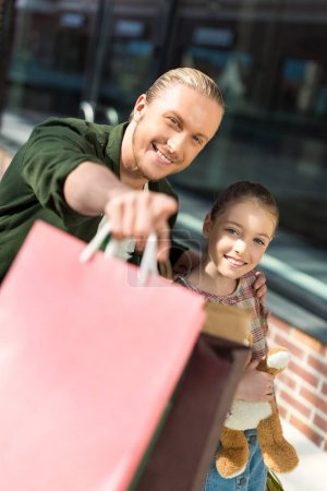 father and daughter holding shopping bags