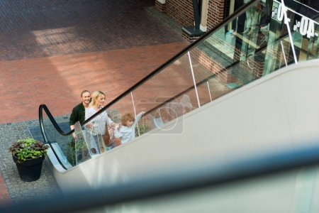 Photo for High angle view of happy parents with cute little son standing on escalator in shopping mall - Royalty Free Image