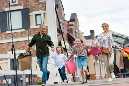Photo for Happy family with shopping bags holding hands and walking while shopping - Royalty Free Image