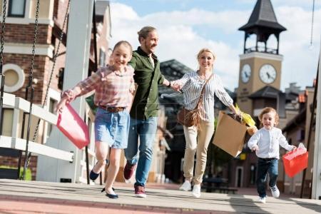 Familie läuft mit Einkaufstüten auf der Straße