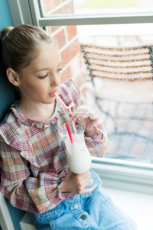 girl drinking milkshake near window
