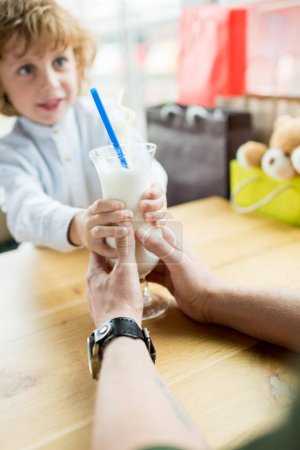 Photo for Selective focus of boy and father holding glass of milkshake together in cafe - Royalty Free Image