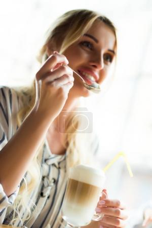 Photo for Selective focus of smiling woman holding teaspoon with coffee cream - Royalty Free Image
