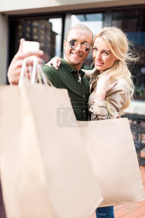 Photo for Young couple taking selfie on smartphone with shopping bags on street - Royalty Free Image