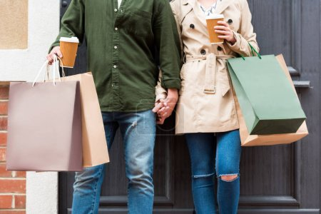 Photo for Cropped shot of casual couple standing with shopping bags and drinking coffee on street - Royalty Free Image