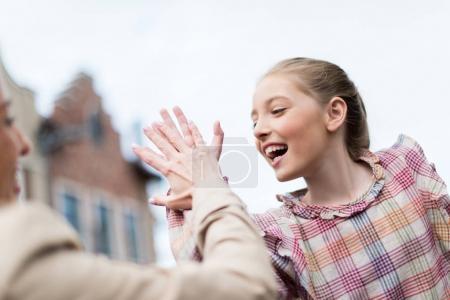 Photo pour Portrait de fille émotive donnant cinq élevés à sa mère - image libre de droit