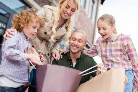 Photo pour Heureuse famille caucasienne regardant dans le sac à provisions dans la rue - image libre de droit