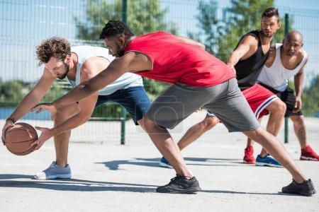 Photo pour Groupe de jeunes hommes multiculturels, jouer au basket sur Cour - image libre de droit