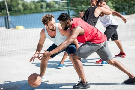 Photo for Group of young multicultural men playing basketball on court - Royalty Free Image