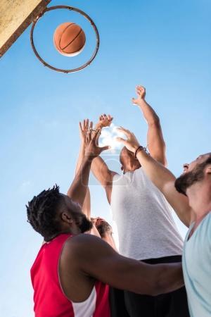 Photo pour Vue à faible angle des joueurs de basket multiculturels qui luttent pour attraper le ballon - image libre de droit
