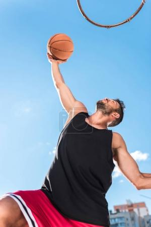 Photo for Low angle view of basketball player throwing ball into basket - Royalty Free Image