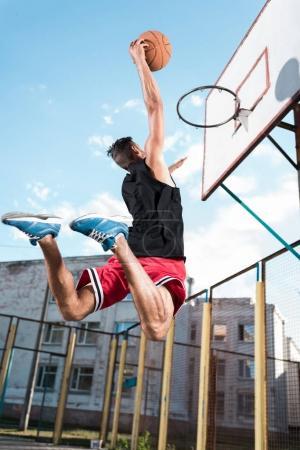 Photo pour Vue arrière du basketteur, lancer la balle dans le panier au cours du jeu - image libre de droit