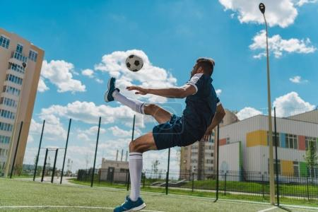 Photo for Athletic soccer player kicking ball on soccer pitch - Royalty Free Image