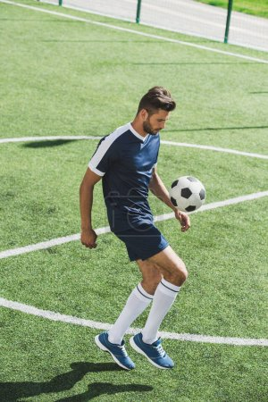 Photo for Side view of soccer player kicking ball  while training on soccer pitch - Royalty Free Image