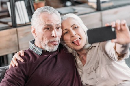 Photo for Grimace senior couple sticking tongue out and taking selfie while resting on sofa at home - Royalty Free Image