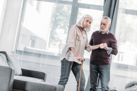 Photo pour Homme aidant femme âgée avec bâton de marche à marcher à la maison - image libre de droit